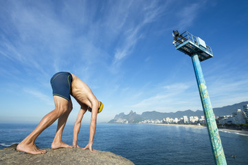 Athlete swimmer with yellow swimming cap crouching in the start position for a race in front of a skyline view from Arpoador, Rio de Janeiro, Brazil