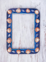 Grunge picture frame with seashells on wooden background