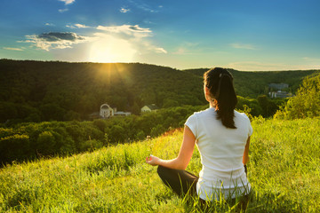 Girl is engaged in meditation on the nature