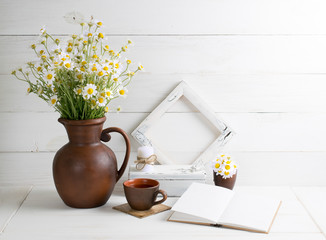 Daisy bouquet with book and cup tea