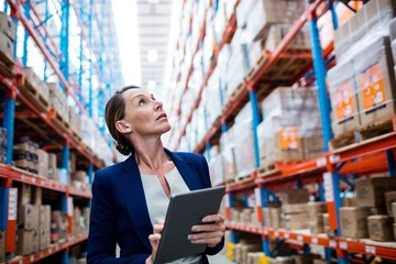 Warehouse manager looking up and taking notes