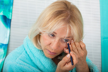 Mature blonde woman putting on mascara at home
