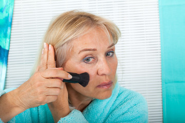 Beautiful senior woman applying make up holding a brush