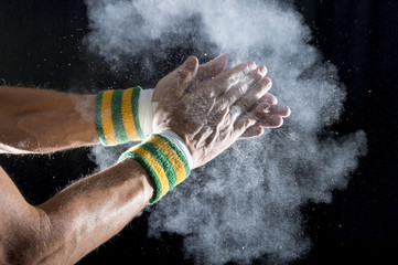Taped hands of gymnast wearing Brazil colors wristbands clapping white chalk powder into a cloud against dark background