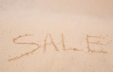 sale handwritten in sand on a beach