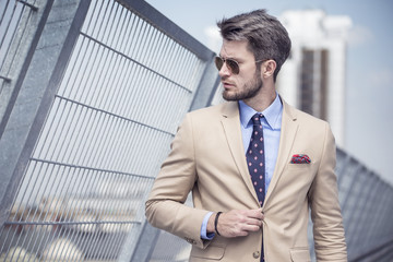 Handsome man in bright suit against the city