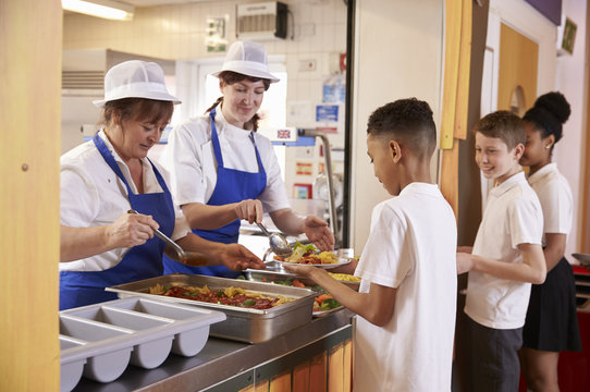 Two women serving food to a boy in a school cafeteria queue