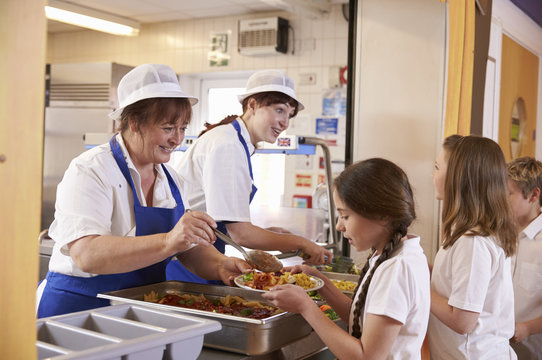 Two women serving food to a girl in a school cafeteria queue