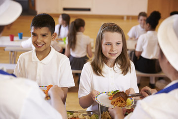 Over shoulder view of kids being served in school cafeteria