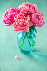 Close-up floral composition with a pink peonies on a green background with old paper texture.