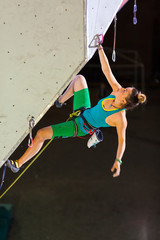 Cute female Athlete hanging on climbing Wall