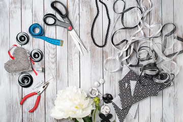 Scissors, buttons, accessories on white wooden background. Handmade workplace. Top view.