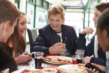 Teenagers Eating Pizza In Cafe And Looking At Mobile Phone