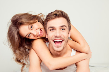 Fototapeta Cheerful smiling couple in love hugging in the bedroom