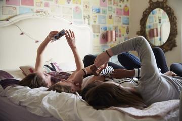 Teenage Girls Using Mobile Phones In Bedroom At Home