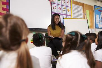 Teacher Reading To Elementary School Pupils In Classroom