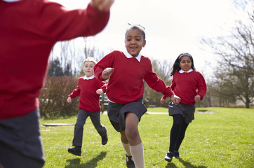 Elementary School Pupils Running In Playground At Breaktime