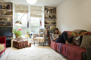 Young woman reading book while lying on sofa