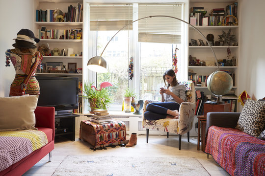 Woman Relaxing Using Mobile Phone In Stylish Apartment