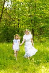 Beautiful family goes hand in hand. Happy family resting on the nature in the summer. Mom and daughter with wreath in the flowers in the park