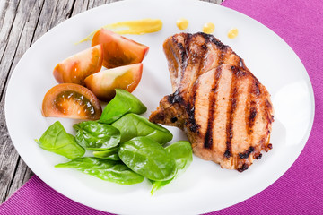 grilled pork chops with slices of black tomatoe and spinach leav