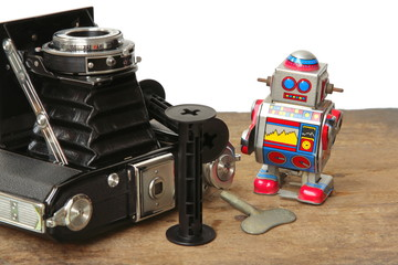 Tin robot toy with Antique Vintage Retro Old Photo Camera compose on wooden plank on white background