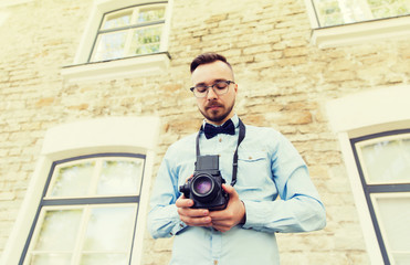 happy young hipster man with film camera in city