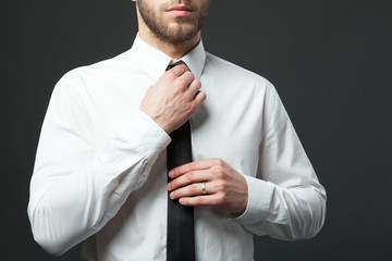 Mid section of young fit businessman adjusting tie isolated.