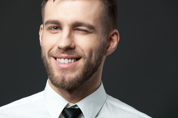 Studio portrait of handsome young businessman smiling and winkin