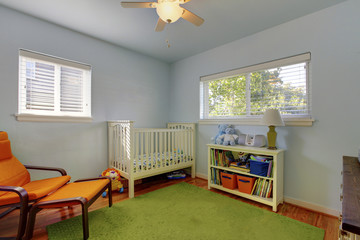 Colorful interior of kids bedroom with wooden white cirb and gre