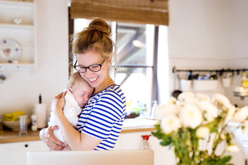 Happy mother with baby in kitchen looking at laptop