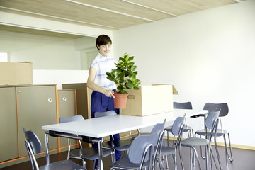 Woman with potted plant in new office