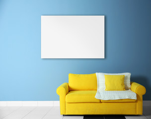 Yellow sofa and empty picture frame on blue wall background