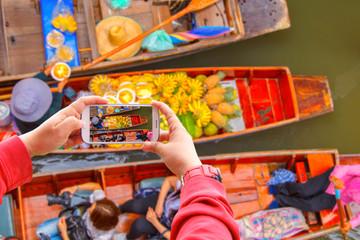 Smartphone photographing Damnoen Saduak floating market in Ratchaburi near Bangkok, Thailand