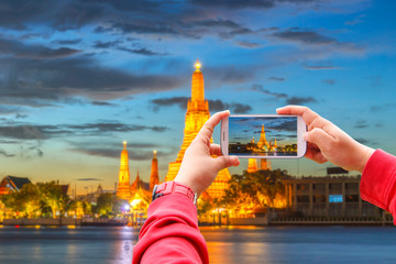 Smartphone photographing Wat Arun Buddhist religious places in twilight time, Bangkok, Thailand