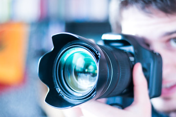 Junger Mann fotografiert mit Spiegelreflexkamera