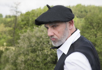 Portrait image of a mature man with a serious facial expression, wearing a black beret and a scarf, in the countryside. Taken with a blurred background