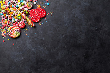 Colorful candies and lollipops over stone