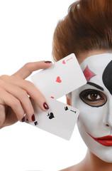 Girl in image of joker with cards in studio shoot