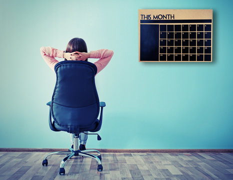 Woman sitting back on the office chair and looking at chalkboard calendar on wall background