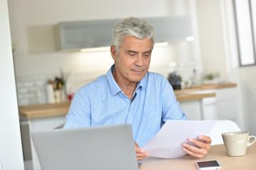 Smiling senior man at home using laptop