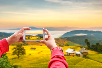 Smartphone photographing Sunrise at Terraced Paddy Field in Mae-Jam Village , Chiang Mai Province , Thailand