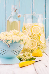 Elderflower and lemon slices in a jug for making elderflower syrup.