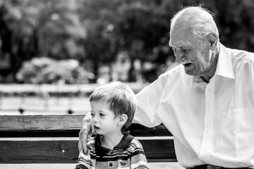 grandfather taking care of grandchild black and white