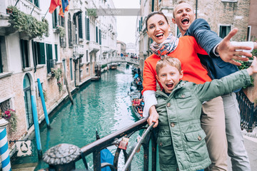 Happy family take a selfie photo on the one of bridge in Venice