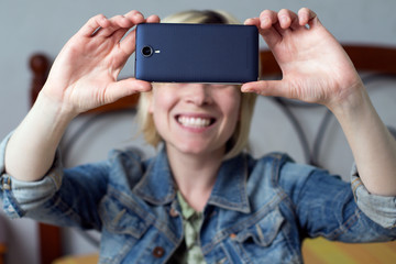 Blonde woman holding a mobile, smiling and  making a selfie in the room
