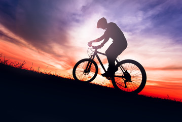 Silhouette of a biker on bike with sky background on sunset.