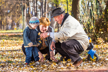 grandparents playing with grandson in a park