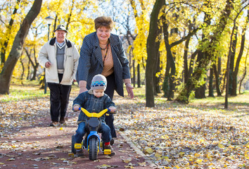 happy grandparents and grandchild have fun and play in park