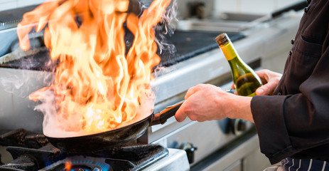 Chef doing flambe to food in pan with alcohol